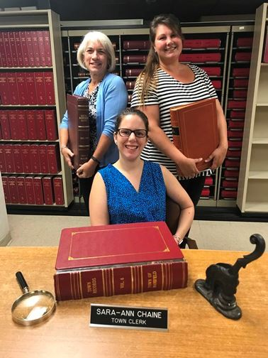 Town Clerk staff holding books and records